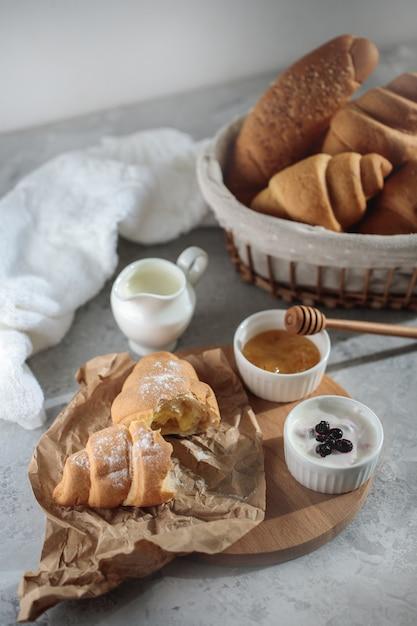 Saboroso café da manhã com croissant francês, com uma tigela de mel e creme. doces frescos. fechar-se. Foto Premium