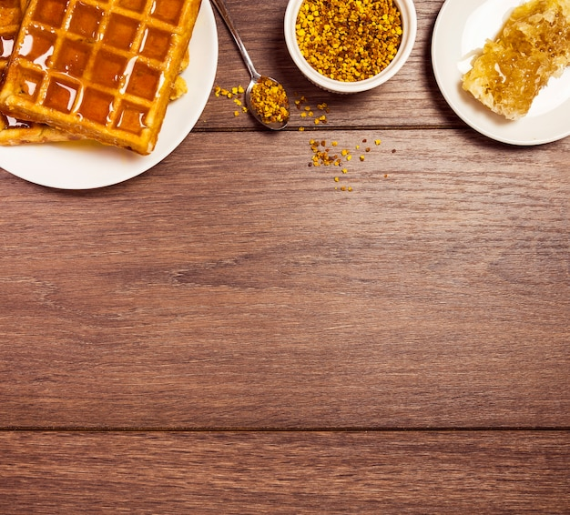 Saboroso café da manhã com waffle; doce mel e pólen de abelha sobre a mesa de madeira Foto gratuita
