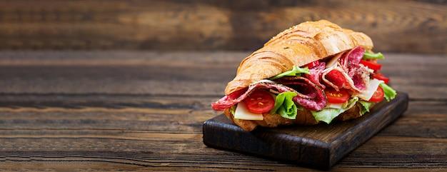 Saboroso café da manhã. croissant apetitoso com salame e queijo e tomate Foto gratuita