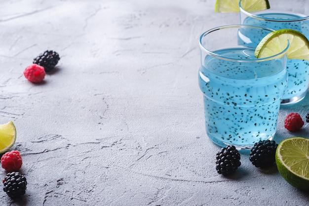 Saboroso coquetel de cor azul com sementes de chia de manjericão, fatia de limão cítrico, framboesa e amoras silvestres em dois copos Foto Premium