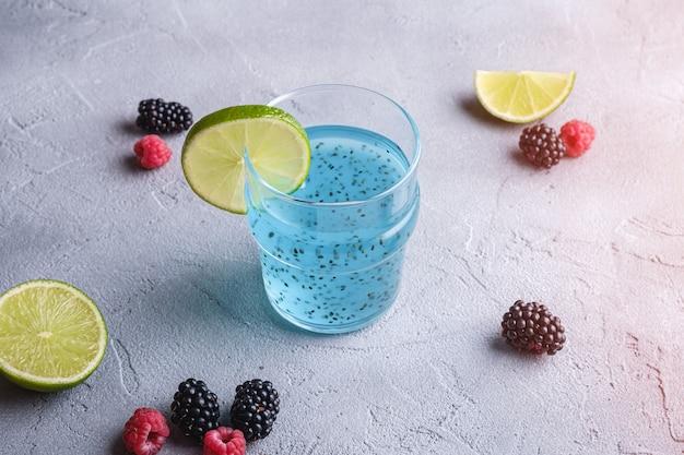 Saboroso coquetel de cor azul com sementes de manjericão chia, fatia de limão cítrico, framboesa e amoras silvestres em vidro Foto Premium