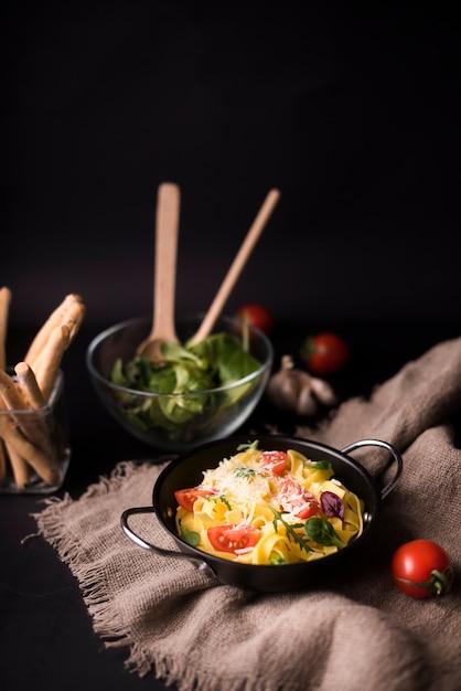 Saboroso macarrão espaguete cozido com folhas de manjericão e tomate no saco com varas de pão e salada veg Foto gratuita