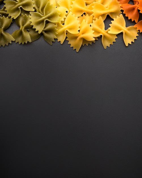 Saboroso macarrão farfalle na superfície preta com espaço de cópia de texto Foto gratuita