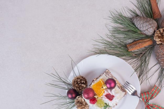 Saboroso pedaço de bolo com pinhas e galho de árvore Foto gratuita