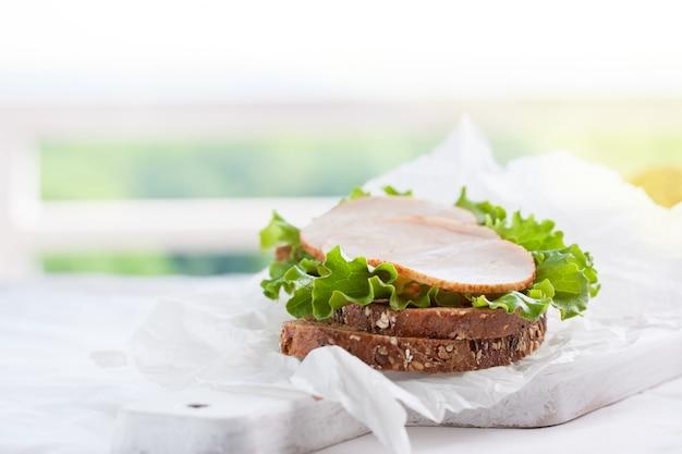 Saboroso sanduíche caseiro com folhas de salada e presunto em uma placa de corte Foto gratuita