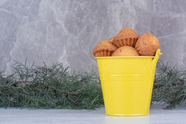 Saborosos bolos pequenos em balde amarelo com galho de pinheiro. Foto gratuita