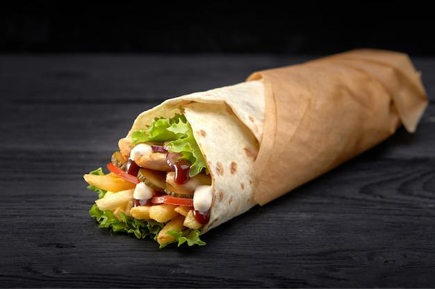 Saborosos espetinhos de doner com guarnições de saladas frescas e carne assada raspada, servidos em tortilhas em papel pardo como lanche para viagem Foto Premium