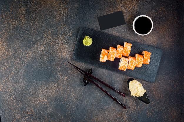 Saborosos rolinhos da califórnia e maki em um prato de pedra com molhos, pauzinhos, gengibre e wasabi Foto Premium