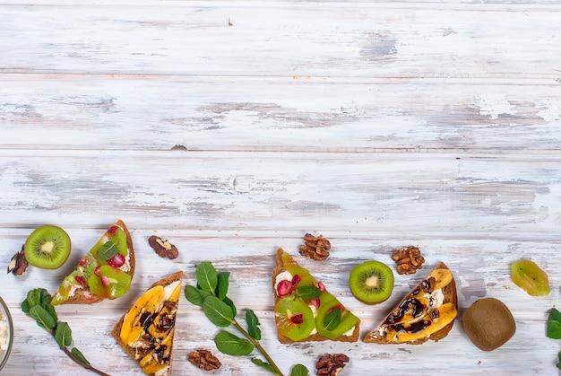 Saborosos sanduíches doces com banana, nozes e chocolate, kiwi, morangos e hortelã na mesa de madeira Foto Premium