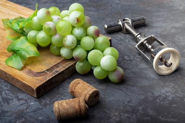 Saca-rolhas com uvas verdes em uma placa de madeira Foto gratuita