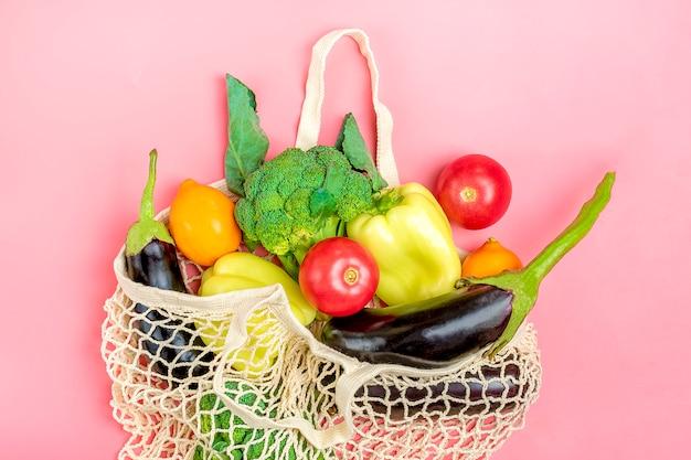 Saco amigável da loja da malha de eco com os vegetais verdes orgânicos na cor-de-rosa. flat leigo, vista de cima. Foto Premium