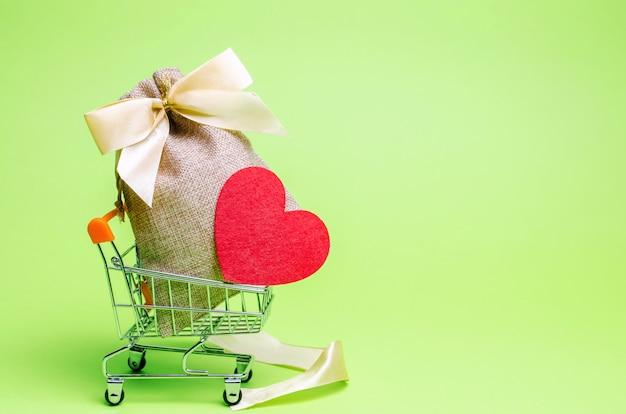 Saco com dinheiro e coração vermelho. dia dos namorados. economizando dinheiro Foto Premium