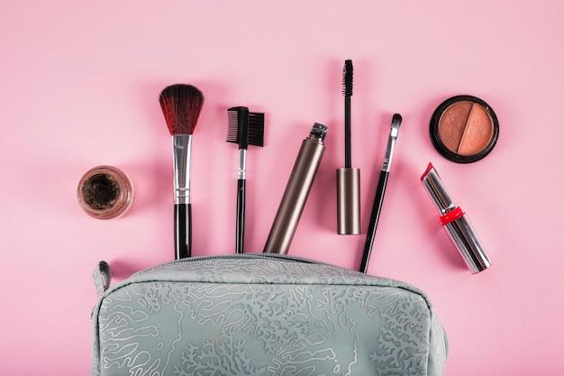 Saco cosmético contendo batom; rímel; delineador e pincéis Foto gratuita