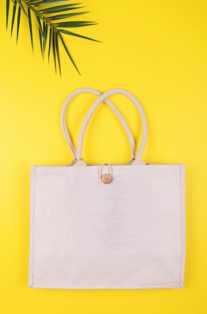Saco de algodão amigável de eco com folha de palmeira em um amarelo, copyspace, estilo mínimo da natureza. reciclagem de conservação ambiental Foto Premium