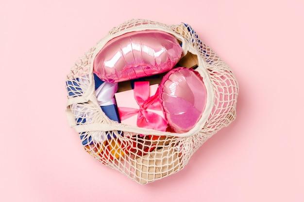 Saco de compras com presente e coração em forma de balão de ar em uma superfície rosa. conceito de presentes para a família, entes queridos, natal, dia dos namorados. . vista plana, vista superior Foto Premium