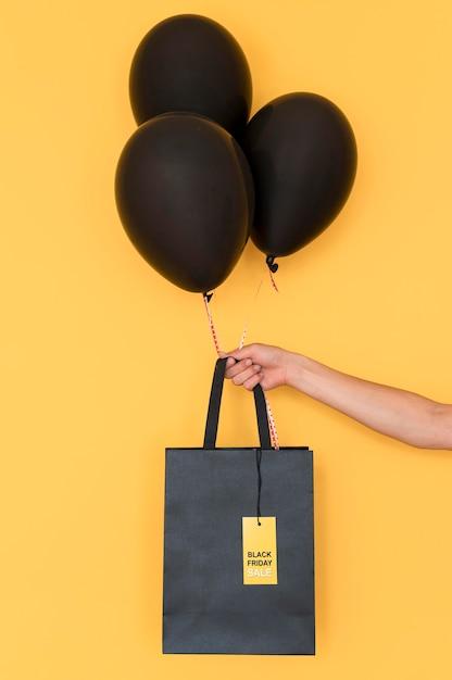Saco de compras preto e balões Foto gratuita