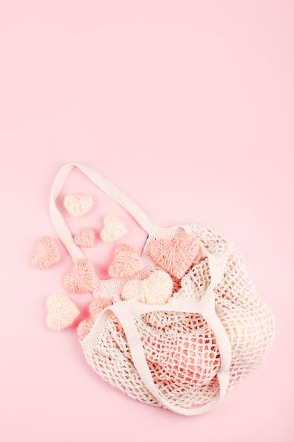 Saco de compras reutilizável com corações de malha brancos e rosa em fundo pastel Foto Premium