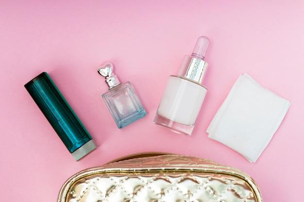 Saco de cosmético ouro sobre um fundo rosa close-up, copie o espaço Foto Premium