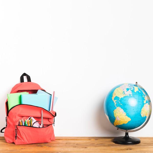 Saco de escola com globo na mesa Foto gratuita