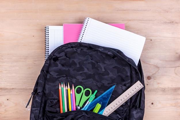 Saco de escola preto com um conjunto de artigos de papelaria para o aluno e com o caderno branco nele. Foto Premium