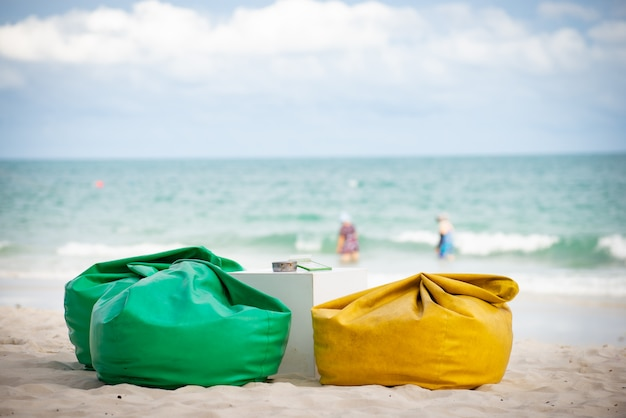Saco de feijão ou sofá e mesa para restaurante na praia Foto Premium