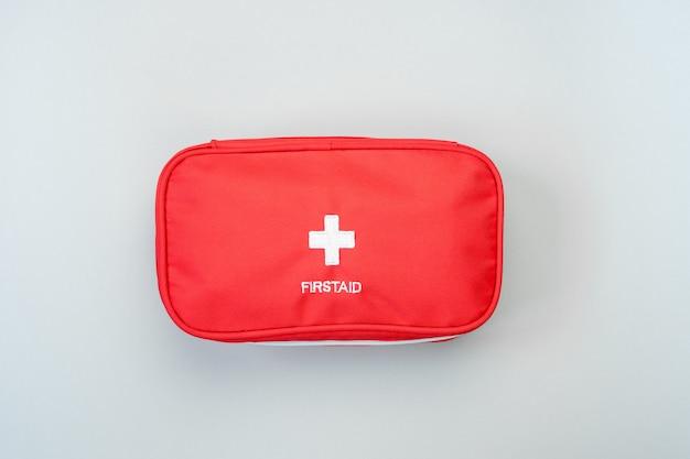 Saco de kit de primeiros socorros vermelho sobre fundo cinza. conceito de tratamento médico de emergência. Foto Premium