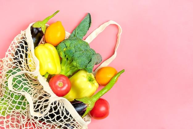 Saco de loja de malha amigável eco com vegetais verdes orgânicos em rosa Foto Premium