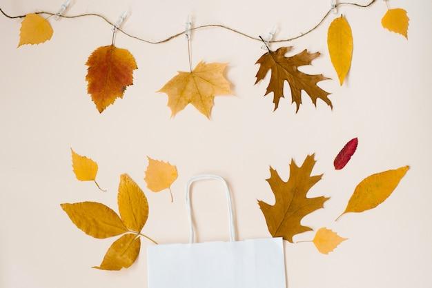 Saco de papel branco com folhas caídas, espreitando de compras Foto Premium