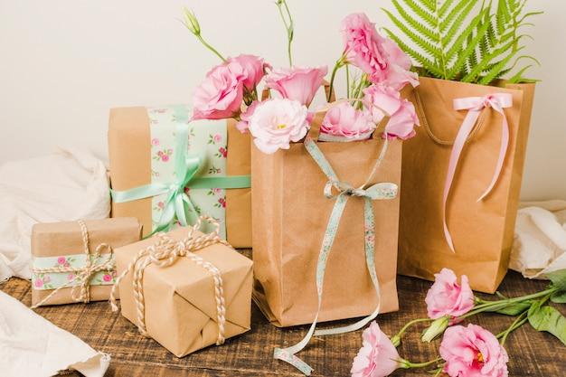 Saco de papel cheio de flores frescas e presente presente embrulhado sobre a superfície de madeira Foto gratuita