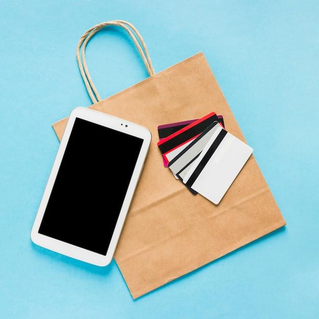Saco de papel com smartphone e cartões de crédito Foto gratuita