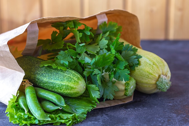 Saco de papel de diferentes vegetais verdes saudáveis na mesa escura. o conceito de nutrição adequada e alimentação saudável. comida orgânica e vegetariana. vista superior, plana leigos, copie o espaço para texto. Foto Premium