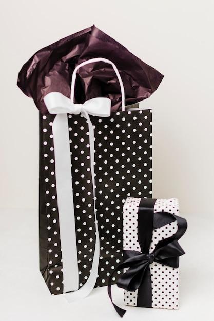 Saco de papel decorativo e caixa de presente bonita contra um pano de fundo branco Foto gratuita