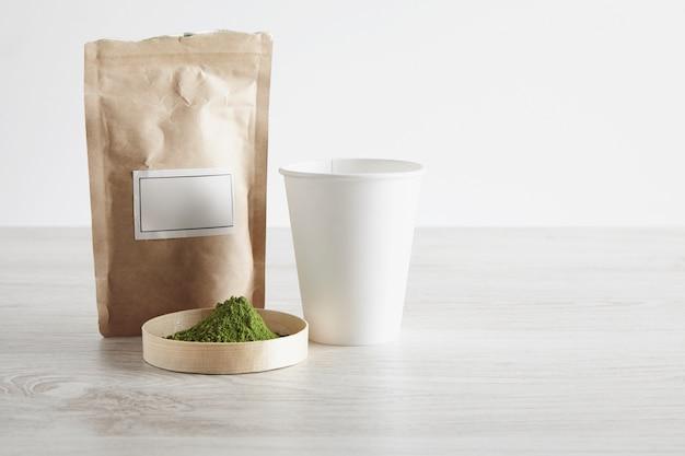 Saco de papel marrom artesanal, vidro para levar e pó de chá matcha orgânico premium em caixa na mesa de madeira branca isolada no fundo simples. pronto para preparar, apresentação de venda. Foto gratuita