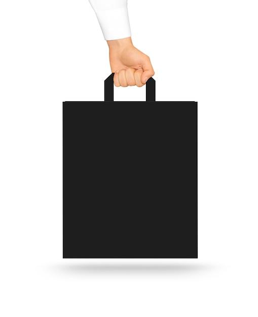 Saco de papel preto em branco simulado até segurando na mão. Foto Premium