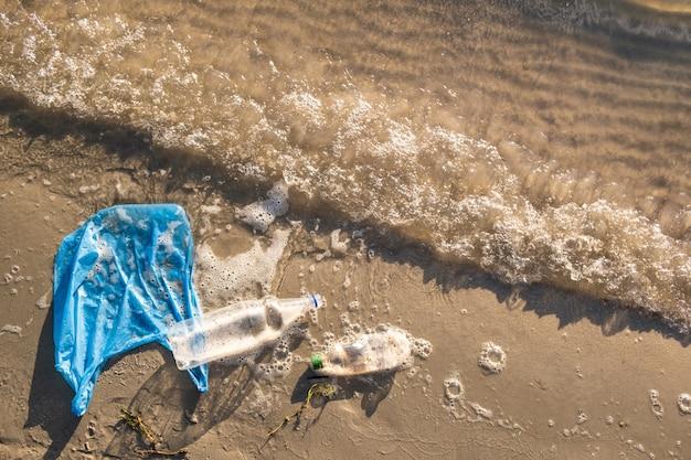 Saco de plástico e garrafas no conceito de poluição de praia, litoral e água. lixo (pacote de comida vazio) jogado fora à beira-mar, vista superior com ondas de água e areia Foto Premium