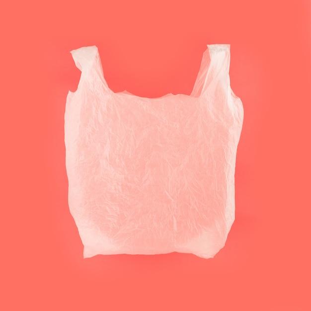 Saco de polietileno branco sobre fundo de papel coral vivo Foto Premium
