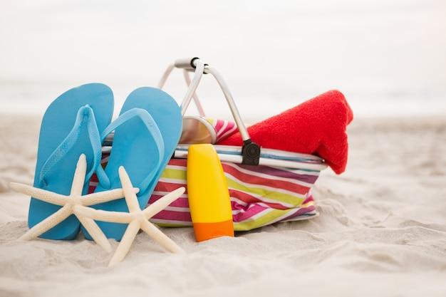 Saco de praia e acessórios mantidos na areia Foto gratuita