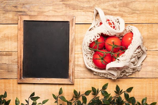 Saco de tomate ao lado de lousa vazia Foto gratuita