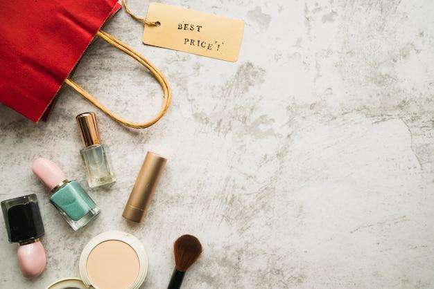 Sacola de compras com pequena tag perto de batom e unha polonês Foto gratuita