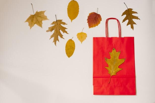 Sacola de papel vermelho com folhas de outono Foto Premium