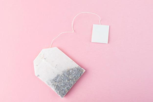 Sacos de chá com etiquetas brancas no fundo da superfície rosa pastel Foto Premium