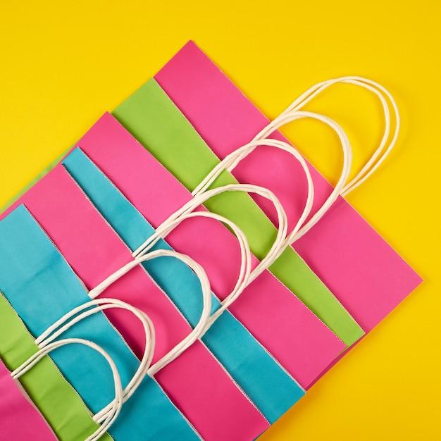 Sacos de compras de papel colorido multi com alças brancas Foto Premium
