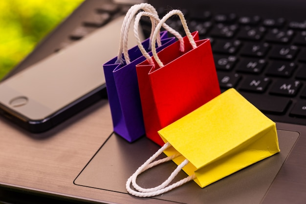 Sacos de compras de papel pequeno com telefone móvel em um teclado de laptop Foto Premium