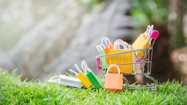 Sacos de compras em um carrinho de compras com grama natural. Foto Premium