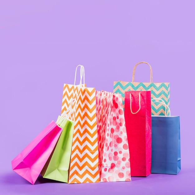 Sacos de compras vazios coloridos no fundo roxo Foto gratuita