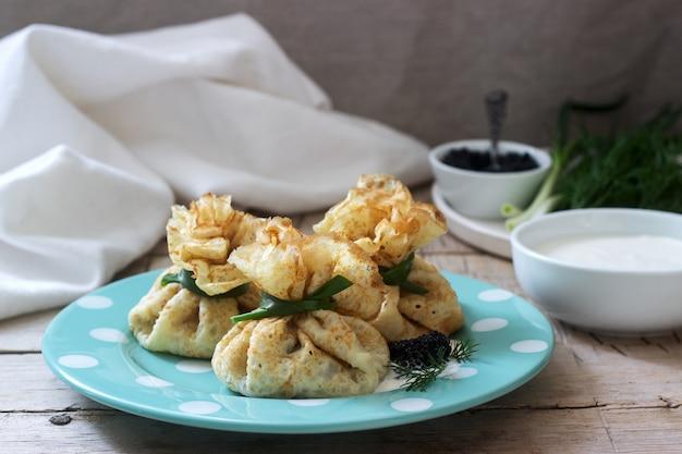 Sacos de panquecas recheadas com arenque, servido com caviar, creme de leite e endro em um fundo de madeira. estilo rústico. Foto Premium