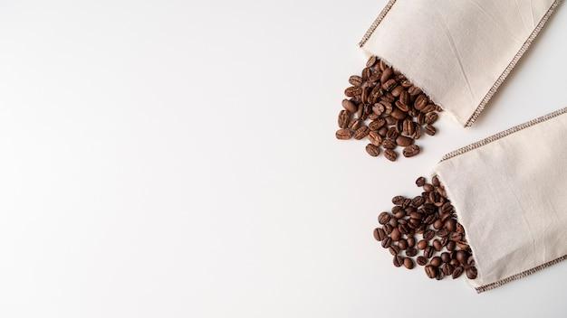 Sacos de papel com superfície branca de grãos de café Foto gratuita