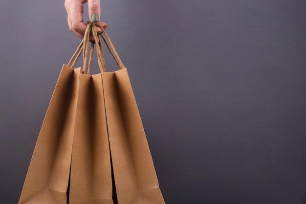 Sacos de papel kraft nas mãos da mulher na superfície escura brilhante. Foto Premium