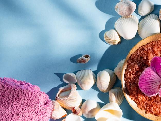 Sal de banho alaranjado em um pires com conchas, toalha e flor em um fundo azul com uma sombra de uma planta tropical. copyspace, flatlay. spa, relaxado, verão Foto Premium