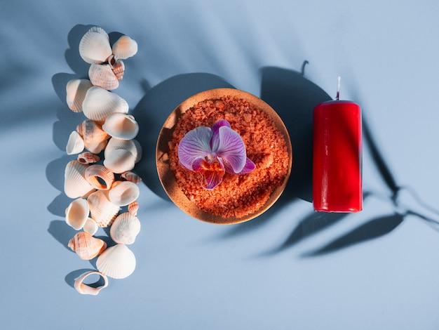 Sal de banho laranja em um pires com conchas, vela vermelha e flores sobre fundo azul com uma sombra de uma planta tropical. copyspace, flatlay. spa, relaxado, verão Foto Premium